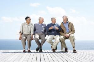 Vier ältere Männer sitzen auf einer Bank am Wasser während einer von ihnen etwas erklärt
