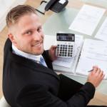 Geschäftsmann mit Taschenrechner vor Papieren am Schreibtisch